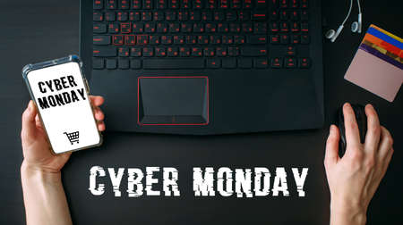 Woman's hands using laptop and smartphone for shopping online at home while Cyber Monday Sales. Top view of the workspace on black background. Promotion inscription on screen.