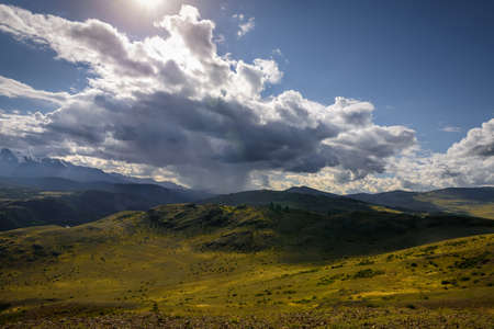 Mysterious mountain landscape with storm clouds hills and sun rays. Beautiful sky. Green grass on hills shimmers in the sunlight. Photo with tinting. Wallpaper for desktop or smartphone.