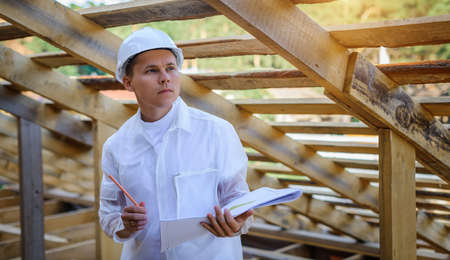 Young male engineer looking at construction work. Foreman in white clothes inspect constructing area. Architect holding blueprint of wooden frame. Wearing helmet for safety. Labor day concept.