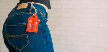 People, sale, consumerism concept. Close up cropped photo of sexual woman's buttocks wearing blue casual denim pants on gray brick background in the mall. Red tag black Friday on jeans. Copy space.
