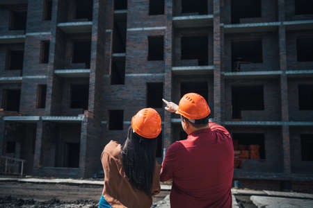 Rear view builders a man and a woman in orange helmets stand on the background of a brick apartment building under construction. Foremen monitor the progress of construction of the object.