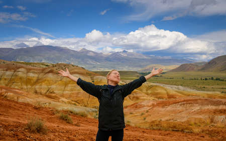 Happy female traveler raising her hands up against the beautiful mountains and blue sky with white clouds on sunny day. Cheerful young woman enjoying trip and freedom.