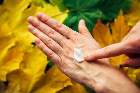 Female hands applying moisturizing cosmetic cream, close up. Blurry background of autumn foliage. Dry skin needs to hydrated and nourished. Concept of adulthood, reduced collagen production.