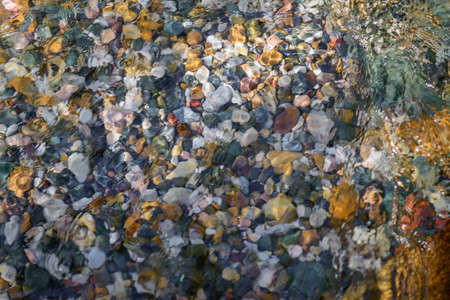 Rocky bottom of mountain stream, close-up. Colorful stones under clear water. Beautiful distortion background. Natural mosaic of small stones. Image for ceramic tile design, bathrooms.
