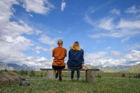 Two young women sitting on wooden bench, backs to the camera against beautiful landscape. Friends travel, admire magnificent view of mountain range under blue sky on sunny day.