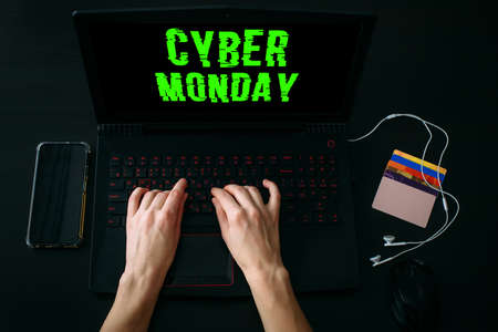 Woman's hands typing on laptop keyboard for shopping online while Cyber Monday Sales. Top view of the workspace with smartphone, credit cards on black background. Promotion inscription on screen.