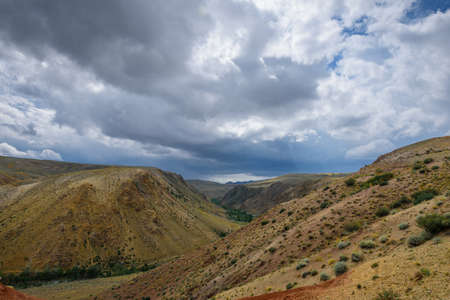 Fantastic deserted landscape. Multi-colored mountains against the sky covered by clouds with sun rays. Red and brown hills. Altai Republic, Siberia, Russia.
