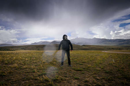 Strange man in black hood and gas mask on the background of mountains, around smoke, fog and radioactive fallout. Concept of environmental pollution, chemical disaster. Ecological catastrophe. 版權商用圖片