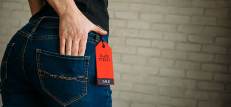 Cropped view slim woman in jeans with label black friday, copy space. Female hands in the back pocket of blue denim pants, close up. 版權商用圖片
