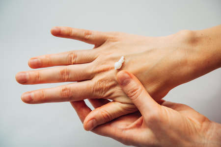Close up female hands applying moisturizing cosmetic lotion, on white background. Woman's adult hands, apply nutrient cream. Skincare, beauty treatment concept. Repair damaged dry skin.