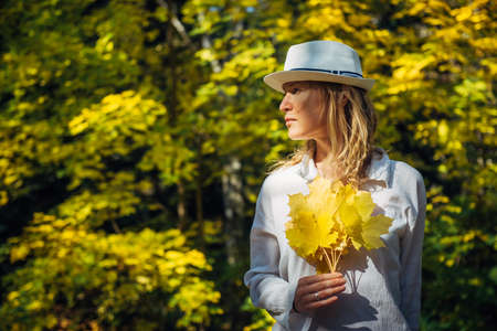 Beautiful elegant woman in white shirt and hat posing with bouquet of autumn leaves in sunny day. Young blonde holds bright yellow maple leaves in her hands. Natural blurred background, copy space. 版權商用圖片