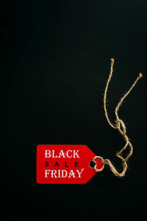 Black friday shopping sale concept. Text on red tag on black wooden background. Vertical image, copy space.
