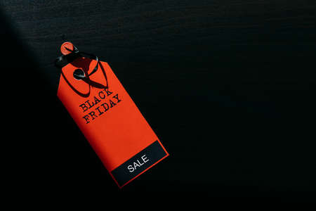 Concept image of label with inscription on dark wooden background, combination of light and shadow. Red tag Black Friday, close-up, copy space.
