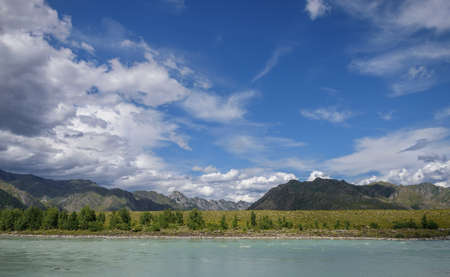 Majestic Katun river surrounded by rocky mountains, wooded banks against a blue sky with white clouds. Beautiful natural landscape.