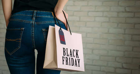 Woman holding a paper bag with tag black Friday. Back view of slender female butt in blue jeans. Concept of shopping, seasonal discounts.
