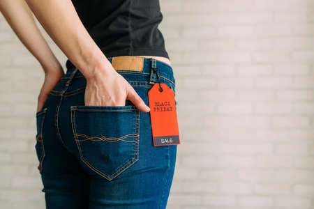 Cropped view slim woman in jeans with label black friday, copy space. Female hands in the back pocket of blue denim pants, close up.