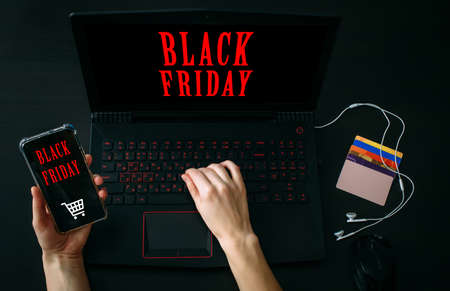 Inscription Black Friday. Online Shopping Concept. Cropped view woman's hand holding smartphone with app and using laptop computer.