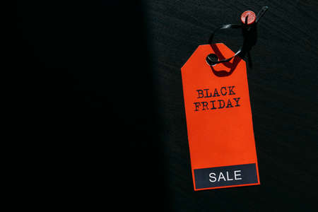 Black friday shopping sale concept. Text on red tag on black wooden background. Copy space.
