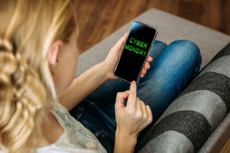 Cyber Monday shopping app in a mobile phone screen. Woman holding smartphone in the hand, lying on sofa. Safety shopping digital technology and electronics from home during the quarantine. 版權商用圖片
