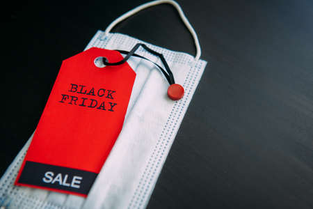 Red tag with the inscription Black Friday on the background of medical mask. Sales in the context of Covid-19 pandemic. Concept of safe shopping.