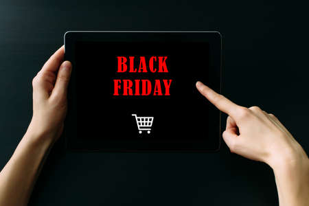 Women's hands holding tablet computer with inscription on screen, dark background, close up. Black friday concept.