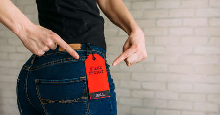 Woman tries on clothes and points to the Black Friday tag. Back view of a slender female butts in blue jeans. Shopping concept, seasonal discounts. Advertising sign. 版權商用圖片