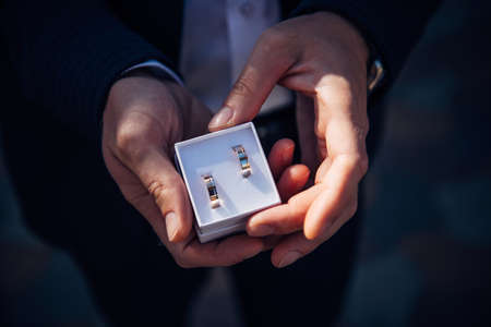 Groom holding small box with gold wedding rings. 免版税图像