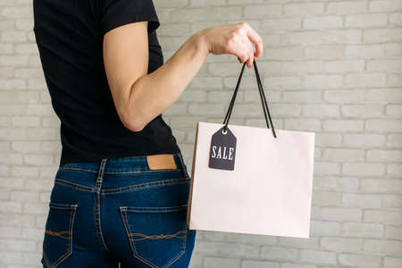 A woman in denim holding paper bag with tag in her hand against a white brick wall 免版税图像