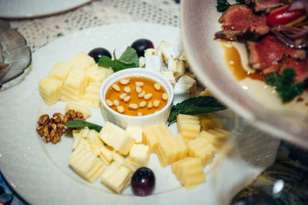 Cheese plate on banquet table, close-up. Dish is served with honey and nuts. Fine food, delicacies.