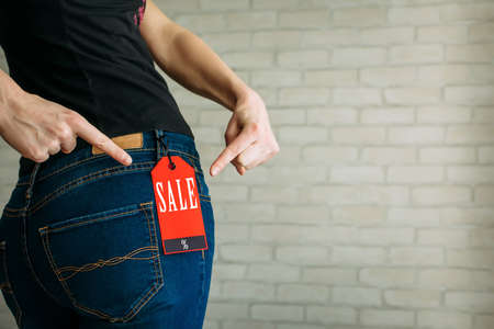 Woman tries on clothes and points to the Black Friday tag.