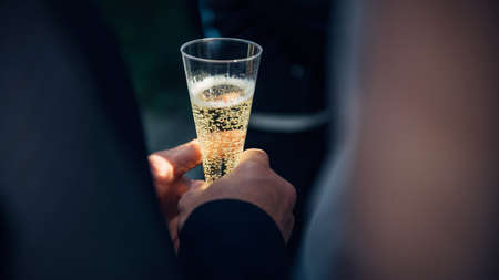 Champagne glass in hand, close-up. Bubbles in cold alcohol drink shimmer in the sun on blurred