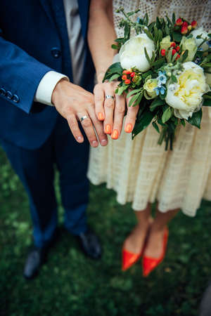 Focus on the hands of bride and groom, wedding bouquet, top view, blurred background. Platinum or silver rings on the fingers of newlyweds, close-up.