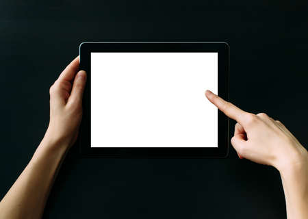 Tablet computer with white blank screen in hands isolated on black background. Holding and pointing to empty screen on digital tablet. Copy space.
