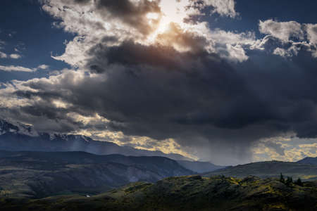 Dramatic dark clouds in mountains before storm. Landscape with mountain range, rain clouds and rays from the sun. Epic natural background. 版權商用圖片