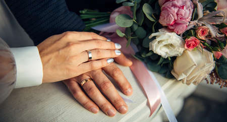 Hands of the bride and groom, wedding bouquet, top view. Gold rings on the fingers of the newlyweds, close-up. 版權商用圖片