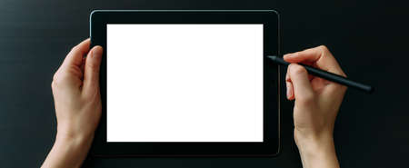 Graphic designer's hands working on tablet with digital pen, close up. Empty white screen, black background.