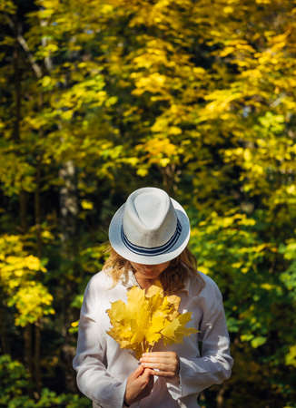 Beautiful young woman in white clothes and hat tilted her head to the bouquet of yellow leaves in her hands. Elegant blonde, face hidden by hat. Freedom, love, happiness. Indian summer, golden autumn. 版權商用圖片