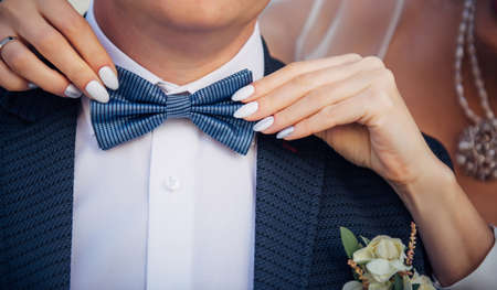 Bow tie on the groom's suit.