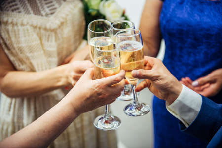 Guests and relatives of different ages at the wedding raise their glasses with festive champagne. Hands with drinks close-up. Marriage celebration, congratulations.