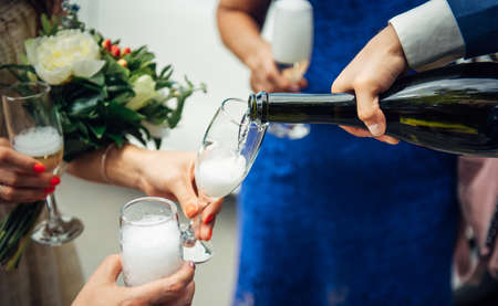 Man fills glasses of champagne for guests at festive dinner. Hand holding a bottle, close-up. Pouring drinks to friends and relatives at wedding banquet. 版權商用圖片