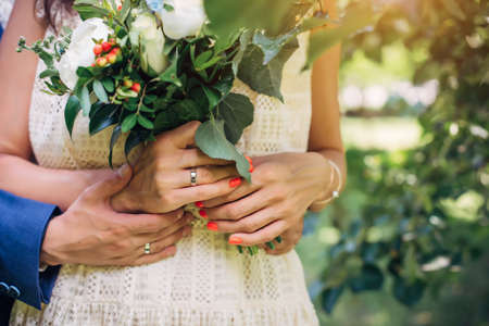 Hands of the bride and groom with wedding rings, bouquet of fresh flowers, vintage lace dress. Husband hugs his wife. Concept of marriage, love, and family life.