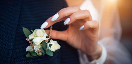 Bride's hand touches the buttonhole on the groom's jacket, close-up. Stylish suit, boutonniere of fresh flowers, woman's hand with a manicure. 版權商用圖片