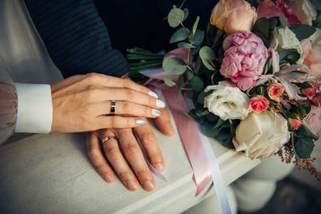 Hands of the bride and groom, wedding bouquet, top view. Gold rings on the fingers of the newlyweds, close-up. 免版税图像