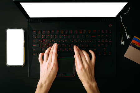 Top view woman's hands typing on laptop with white blank screen. Empty screen smartphone, headphones, credit cards on black background. Mock up, copy space for your text.