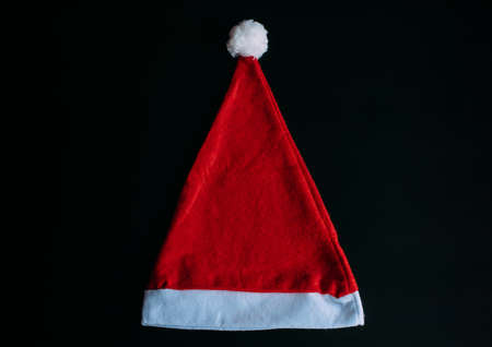 Red Santa Claus hat isolated on black background, top view. Father Christmas cap, close up. New year holidays concept.