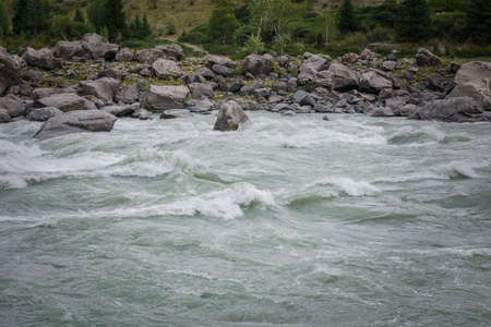 Rapid flow of water in mountain river on the background of rocky banks on cloudy day. Area for rafting, high level of difficulty. 免版税图像