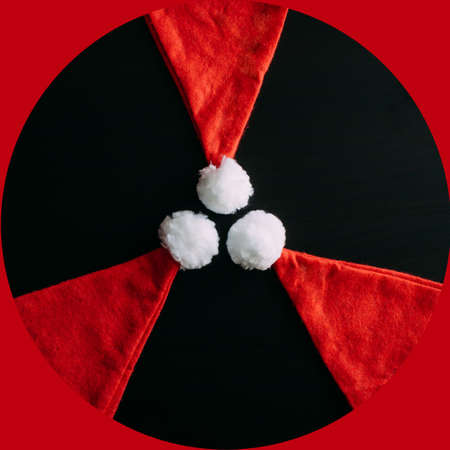 Radiation sign making up of three Santa's caps. Threat of radioactive disease in the new year, environmental pollution, anthropogenic factors. Conceptual image of Santa Claus hats. 免版税图像