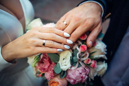 Hands of the bride and groom on the background of wedding bouquet, top view, blurred background. Gold rings on the fingers of newlyweds, close-up.