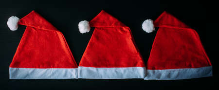 Red Santa Claus hats on black table, top view, close up. Christmas background. New year concept.