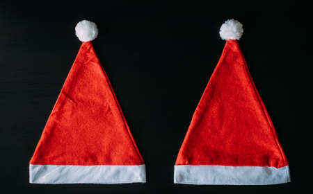 Two red Santa Claus hat isolated on black background with copy space. Father Christmas caps, close up. New year concept. 免版税图像